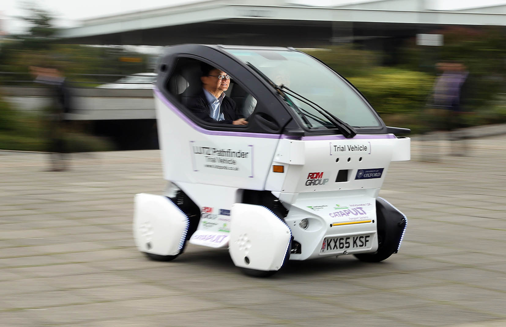 EDITORIAL USE ONLY Eric Chan, Principal Technologist Transport Systems Catapult, takes Harry Hess from Ampthill for a ride as the UK's Transport Systems Catapult unveils its first LUTZ Pathfinder pod vehicle to commuters outside Milton Keynes Central train station, as part of a project trialling self-driving technology in pedestrianised areas. PRESS ASSOCIATION Photo. Picture date: Tuesday September 15, 2015. Following the presentation, the pod will be delivered to Oxford University's Mobile Robotics Group to begin the installation of the vehicle's autonomous control system before undergoing a series of calibration tests to become the first fully automated vehicles on public pedestrianised areas in the UK. Photo credit should read: Geoff Caddick/PA Wire